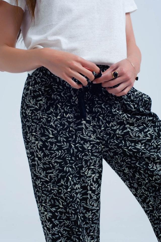 Pantaloni neri con fogli e tasche stampate