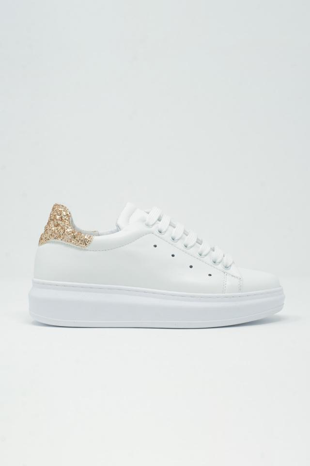 Sneakers spesse bianche e scintillio dorato