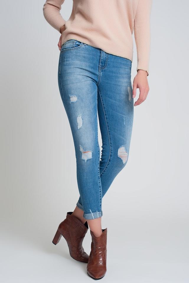 Jeans slim blu lavaggio scuro con strappi vistosi