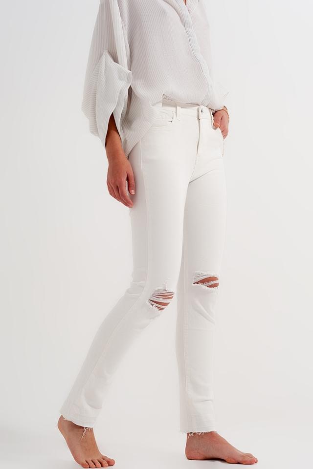 Jeans crema con strappi e fondo sfrangiato